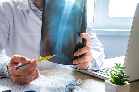 Physician indicates to patient during appointment at elbow radiograph, indicating possible cause and location of disease, such as lateral epicondylitis. Concept photo of diagnosis and treatment