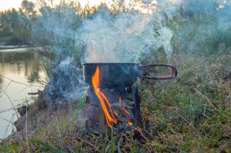 Camping, hiking and adventure photo. Preparing breakfast or tourist morning coffee in camp kitchen fry pan or skillet on portable stove, which burned wood chips on river bank. Visible fire and smoke Imagens - 135502970