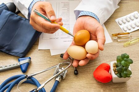 Doctor nutritionist during consultation held in his hand and shows patient raw eggs. Counseling and explanation of use of chicken eggs in food and diet, health benefits, effect on body and organs
