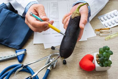 Doctor nutritionist during consultation held in his hand and shows patient eggplant or aubergine. Counseling and explanation of use of eggplant in food and diet, health benefits, effect on body Imagens