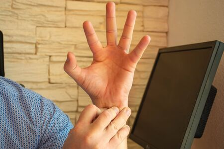 Concept photo of pain in the wrist or forearm, which is accompanied by carpal tunnel syndrome, compression or other nerve or arm joints disease. Man holding on to wrist of other hand, which cramp