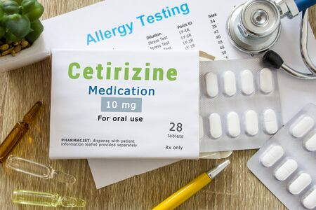 Cetirizine medication or allergy drug concept photo. On  doctor table is pack with words Cetirizine medication and pills for treatment of allergy and hypersensitivity Imagens