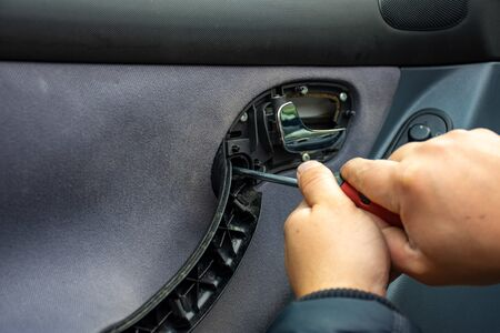 Auto mechanic removes the skin, installs or repairs the handle of the car door, put the glass on the side door, or conducting repairs car lock or window opening mechanism using a manual screwdriver