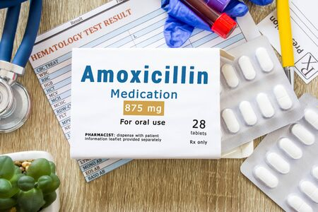 Amoxicillin medication as international nonproprietary or generic name concept photo. Packaging of drug labeled Amoxicillin medication on doctor table with stethoscope Imagens