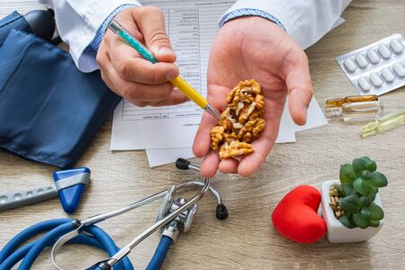 Doctor nutritionist during consultation held in his hand and shows patient walnut kernels. Counseling and explanation of use of walnut kernels in food and diet, health benefits, effect on body Imagens