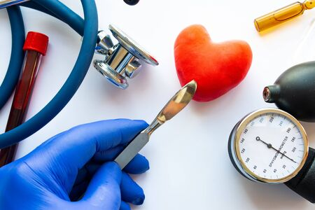 Concept photo of cardiac surgery and heart surgery. Doctor with scalpel in his hand makes an incision in figure of human heart, which is located near medical toolkit - stethoscope and  blood pressure Imagens