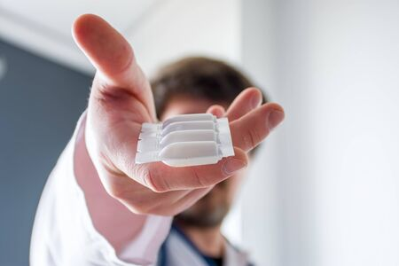 Treatment with medication in form of suppositories concept photo. Doctor  holding in his outstretched hand packaging of suppositories with active curing agent in foreground with focus on packaging Imagens