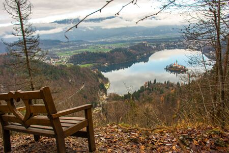 View of Lake Bled in Slovenia from the viewpoint on Mount Velika Osojnica next to a wooden bench on the mountain. Picture taken in late autumn