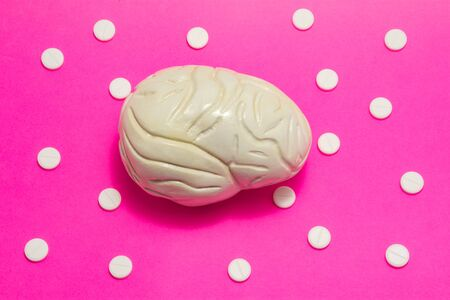 3D anatomical model of brain is on pink background surrounded by white pills as ornament polka dots. Medical concept by pharmacological tableted treating of brain and neurology disease pharmacotherapy Imagens