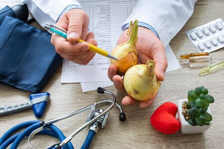 Doctor nutritionist during consultation held in his hand and shows patient onion bulb. Counseling and explanation of use of onion in food and diet, health benefits, effect on body and organs, immune
