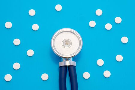 Head of stethoscope is on blue background surrounded by pills or tablets with ornament of polka dots. Concept photo diagnosis, treatment and prevention of various diseases in medicine, use in therapy 写真素材