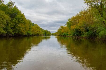 Landscape of Teteriv River, which flows through Ukraine in Europe - photo from boat in  middle of river with overgrown deciduous forest banks with branches hanging over water and dirty water color