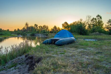 Inverted inflatable boat, pulled out of water to shore, lies near blue tourist tent on  bank of the against background of rising sun over forest. Early morning of tourist, fisherman, traveler Imagens