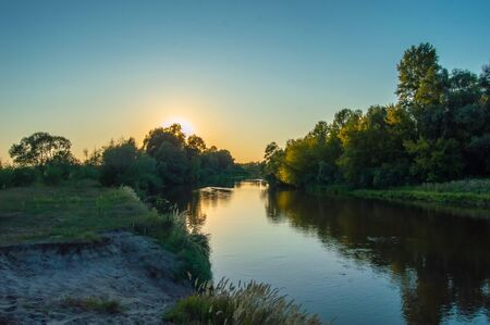 Sunset over the meandering river, which is hidden behind the crown of trees growing on the banks. Photos from the shore. Scenery of Teteriv river, which flows through Ukraine in Europe Imagens - 138733042