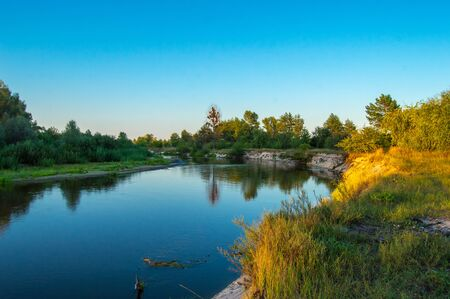 The steep bank of the river, illuminated by the evening sun at sunset against the background of the forest in the distance. Views of the Teterev River, which flow through Ukraine in Europe