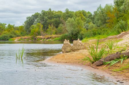 Sandbank in the river in the form of beach with built sandy locks on a background of steep cliffs, overgrown with deciduous forest. Landscape of river Teteriv, which flows through Ukraine in Europe