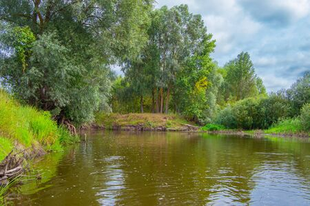 Photo from the boat. Turn of River a right angle with a steep bank with trees on it. Landscape of Teteriv river, which flows through Ukraine in Europe Imagens