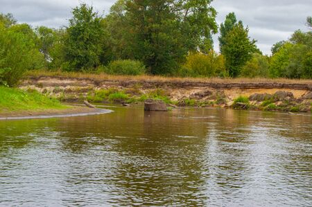 The river turns with a large stump in the water, of sand and steep bank, which was overgrown with woods and bushes. Landscape of Teteriv River, which floats on the territory of Ukraine in Europe Imagens