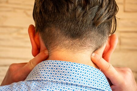 Concept photo of pain in the neck or cervical part spine, inflammation of nerves or neuritis. Person indicates with fingers at localization of neck pain on back surface, exit of occipital nerve
