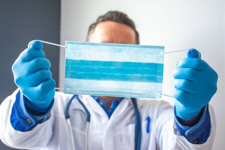 Medical professional, scientist or doctor holds medical mask in outstretched hands near front of camera close-up. Prevention of viral and bacterial diseases transmitted through respiratory - COVID-19