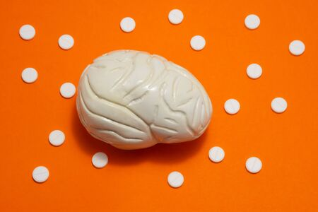 3D anatomical model of brain is on orange background surrounded by white pills as ornament polka dots. Medical concept by pharmacological tableted treat of brain and neurology disease pharmacotherapy