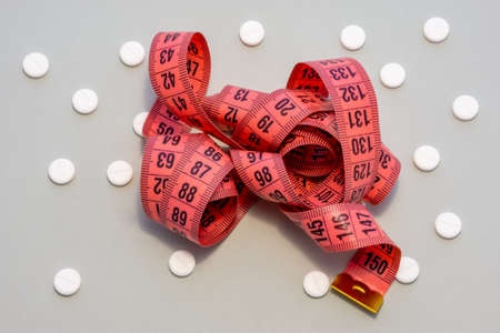 Measuring centimeter tape is on grey background surrounded by white round tablets. Concept photo pharmacological weight loss and use of medicines such as sibutramine, orlistat, metformin