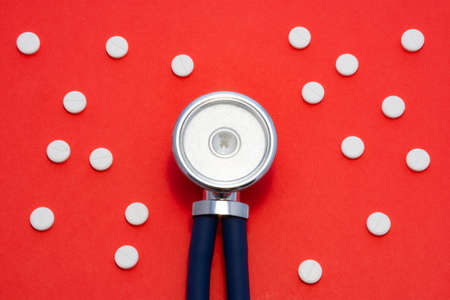 Head of stethoscope is on red background surrounded by pills or tablets with ornament of polka dots. Concept photo diagnosis, treatment and prevention of various diseases in medicine, use in therapy 版權商用圖片
