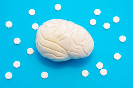 3D anatomical model of brain is on blue background surrounded by white pills as ornament polka dots. Medical concept by pharmacological tableted treat of brain and neurology disease pharmacotherapy