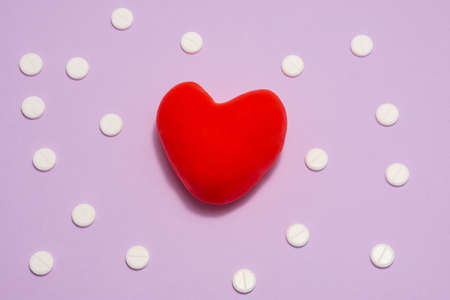 3D anatomical model of heart is on purple background surrounded by white pills as ornament polka dots. Medical concept by pharmacological tableted treating of heart and vessel disease, pharmacotherapy