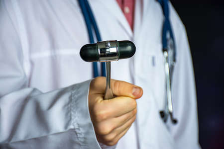 A doctor or neurologist holds a rubber reflex hammer in his hand, demonstrating it to the camera, preparing to conduct a physical examination of the patient. Neurological diagnosis concept photo 版權商用圖片
