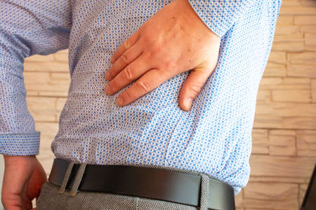 The person holds the right hand behind the back in the area of the kidney and spine. Concept photo of experiencing severe sudden back pain at work