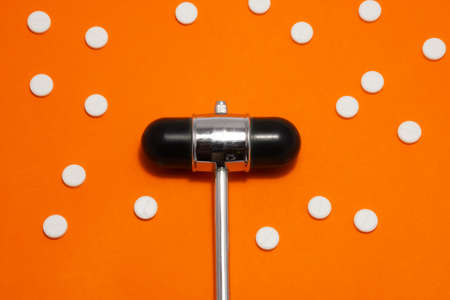 Head of reflex hammer is on orange background surrounded by pills or tablets with ornament of polka dots. Concept photo diagnosis, treatment and prevention of various diseases in medicine, neurology