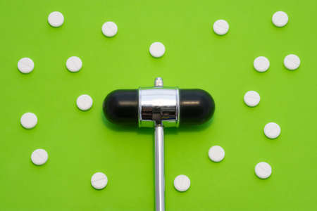 Head of reflex hammer is on green background surrounded by pills or tablets with ornament of polka dots. Concept photo diagnosis, treatment and prevention of various diseases in medicine, neurology