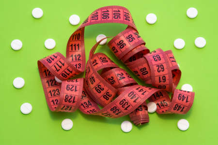 Measuring centimeter tape is on greenbackground surrounded by white round tablets. Concept photo pharmacological weight loss and use of medicines such as sibutramine, orlistat, metformin