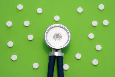 The medical stethoscope is on a green background surrounded by white round pills. The concept of a minimalistic photo to indicate diagnosis and treatment in different areas of medicine 版權商用圖片