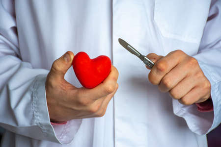 Heart surgery or cardiac surgery (cardiosurgery). Doctor surgeon holding scalpel in hand and cut red heart shape on white background. Concept for surgical operations on heart in adults and children