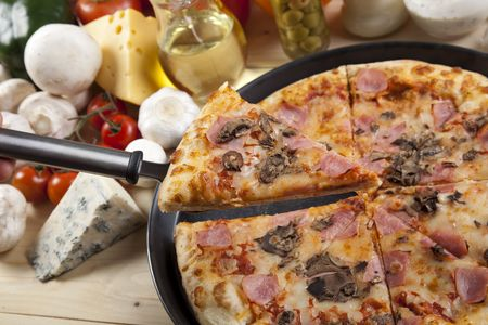A couple of delicious pizzas, with raw tomatoes, green peppers and mushrooms Stock Photo