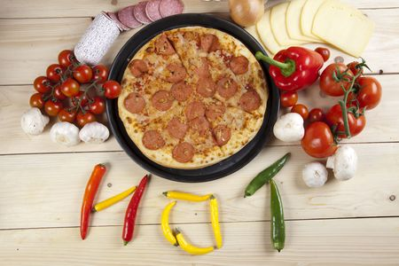 A couple of delicious pizzas, with raw tomatoes, green peppers and salami photo