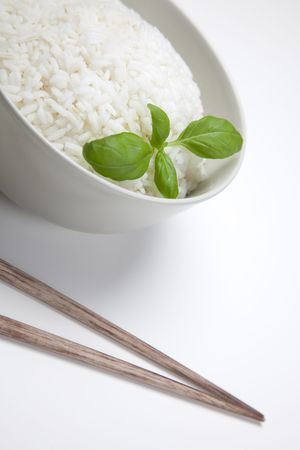 sause: A bowl of perfectly cooked, plain Basmati rice, in an Asian style bowl, with a garnish of Thai Basil