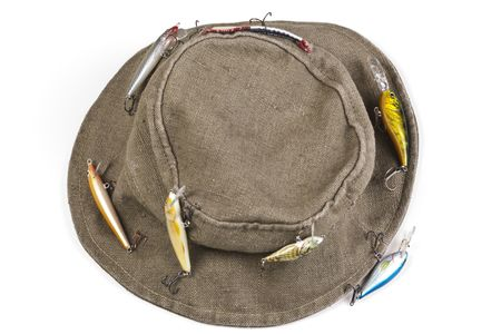 A fishermans hat with lures attached shot against white background with soft shadow Stock Photo