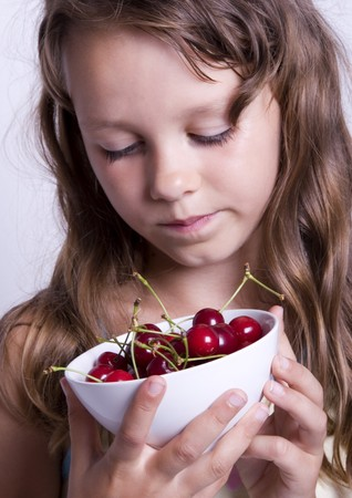 A little girl holding in her hand a cherry photo