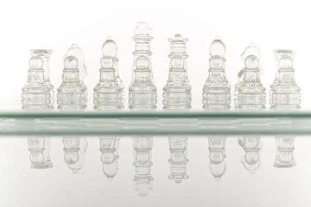 Beautiful glass chess on a white background. Photo taken in the studio on a glass countertop. photo