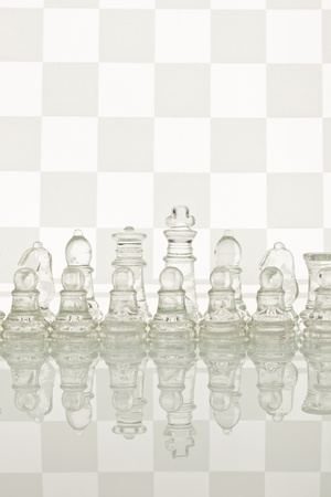 Gass chess on a glass countertop. Checkerboard is the background image. photo