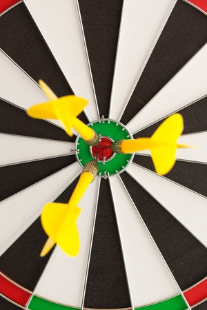 darts flying: Shallow depth of field shot of darts in bullseye on dartboard