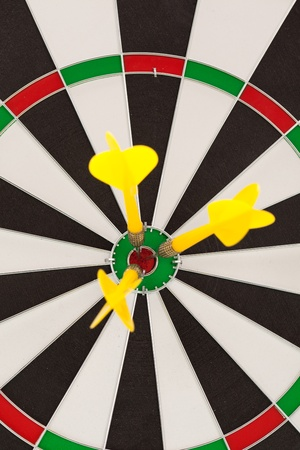 darts flying: Yellow dart hitting the target for the shield Stock Photo