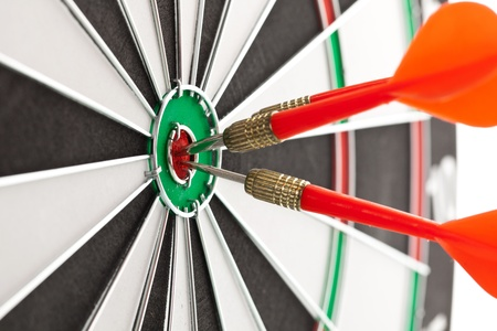 darts flying: Darts hitting the bullseye on a dartboard