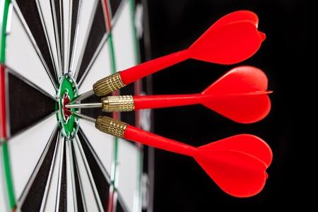 Red darts on black background photo