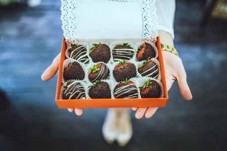 fresa: fresas cubiertas de chocolate. en las manos de la mujer