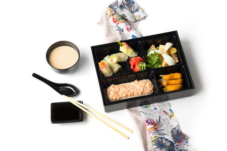 japanese meal: Japanese Meal in a Box Bento isolated on white background - baked salmon with rice, salad with chicken, sushi and rolls Stock Photo