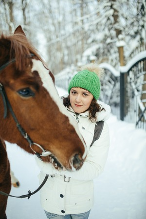 beautiful girl and horse in the winter forest